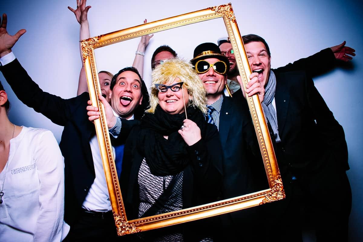 partygäste mit Bilderrahmen vor dem Photobooth
